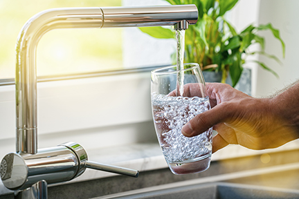 Person filling a glass of water from the tap