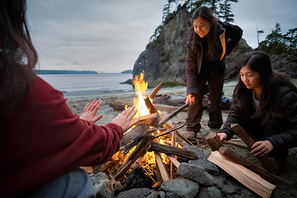 Three sisters gathered around a campfire with water in the background