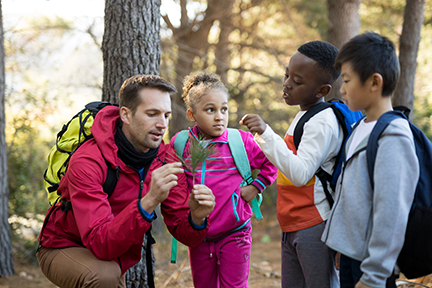 Teacher and kids examining plant in park