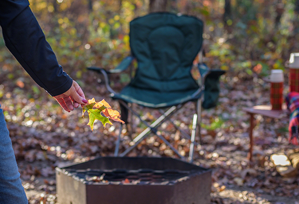 Campsite in fall, with woman holding leaves