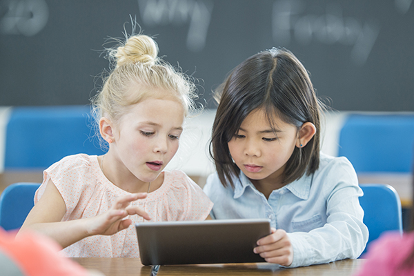 Two elementary school students share a tablet