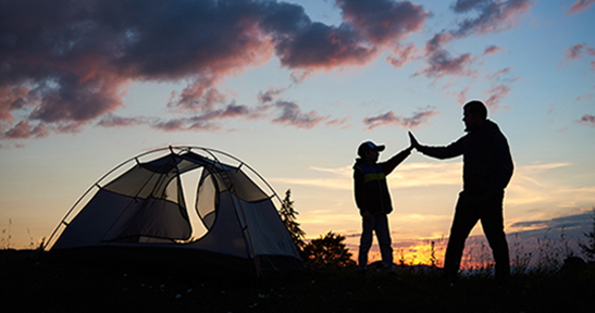 Silhouette of man and child hikers give each other a high five near the tent at dawn